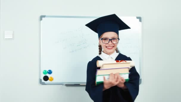 Student 7-8 years graduate in the mantle turns around at camera with books and diploma and smiling with teeth near whiteboard. Slider
