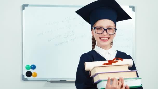 Detailní portrét student 7-8 let absolvent v plášti držící knih a diplomových a směje se zuby u tabule. Jezdec