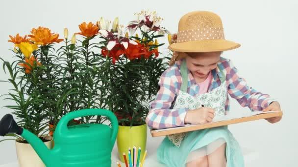 Portré virág-lány gyermek közelében virágok, rajz, a rajz fedélzet és fogakkal mosolyogva ült