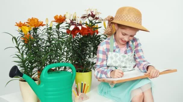 Közelkép portré gyermek lány virágok közelében ült, és a rajz, a rajz fedélzet