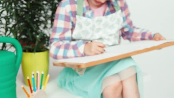 Közelkép portré lány gyermek közelében virágokat ül, és a rajz, a rajz fedélzet