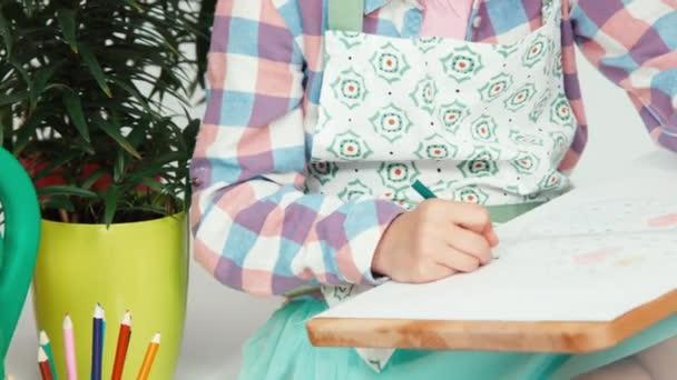 Közelkép portré gyermek lány ül, virágok és rajz, a rajz fedélzet és mosolygós, fogak, a kamera közelében