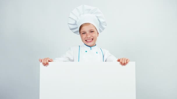 Kuchař za tabule a usmívá se na fotoaparát s zuby. Izolované na bílém. Palec nahoru. Ok