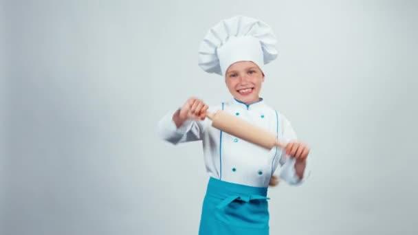 Szakács szakács gyermek tánc a rolling pin, fehér háttér, és mosolyogva kamera 7-8 év