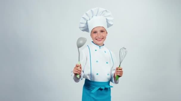 Szakács szakács gyermek 7-8 éve tart, leves merőkanál, és habverővel fehér háttér előtt állt, és mosolyogva kamera