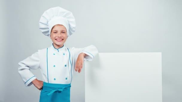 Koch Koch Kind 7-8 Jahre zeigt auf Whiteboard und lächelt in die Kamera mit Zähnen. isoliert auf weiß. Daumen hoch. ok