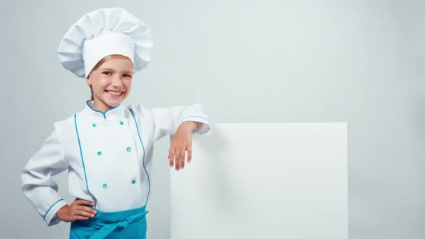 Kuchař kuchař dítě u tabule a usmívá se na fotoaparát s zuby. Izolované na bílém. Palec nahoru. Ok
