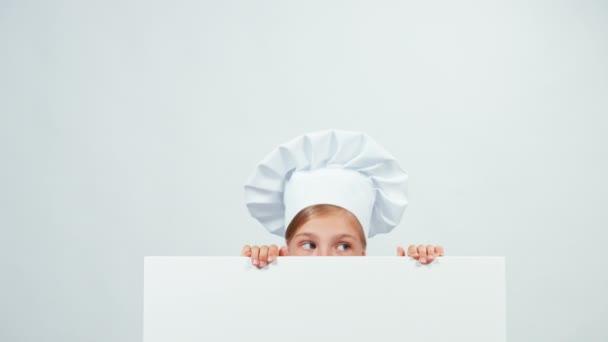 Šéfkuchař se skrývá za tabule při pohledu na fotoaparát a směje se zuby. Izolované na bílém. Palec nahoru. Ok