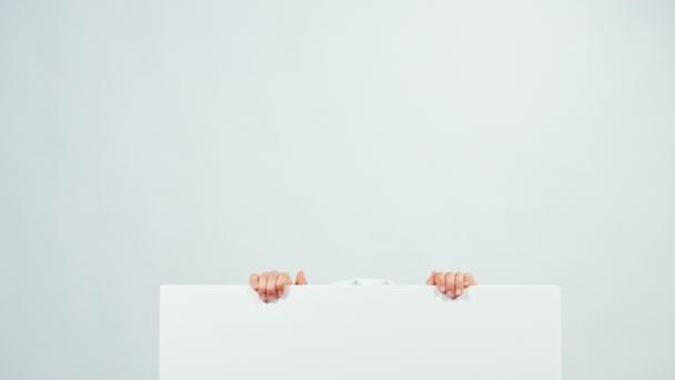 Nahaufnahme Portraitkoch 7-8 Jahre versteckt sich hinter dem Whiteboard und lacht in die Kamera. isoliert auf weiß