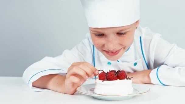 Közelről portré, kis szakács szakács díszítő csokoládé forgács torta és mosolyogva kamera