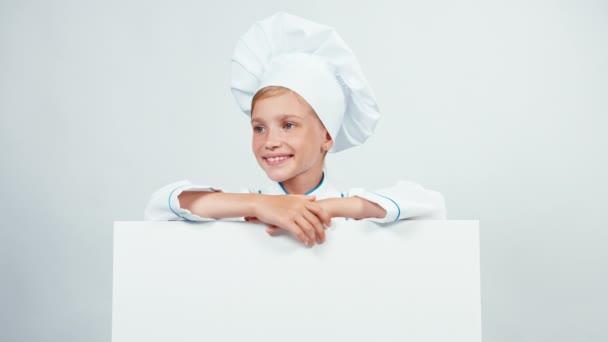 Zblízka portrétní malý kuchař kuchař s bílou tabuli izolované na bílé se usmívá na kameru