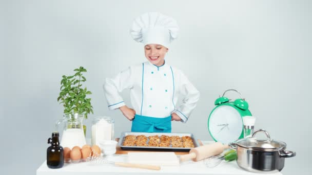 Happy chef cook girl child 7-8 years old has baking tray with biscuits and smiling at camera. Hand ok. Isolated on white background