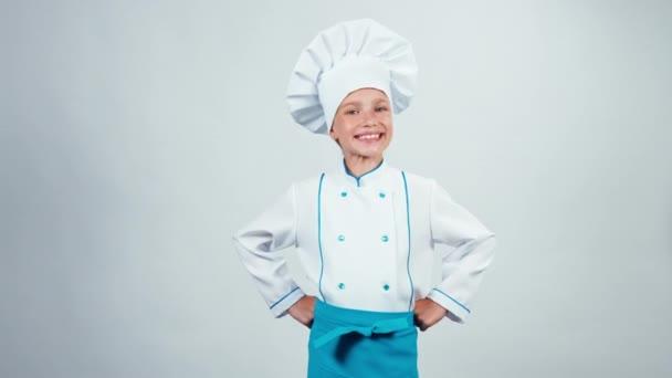 Portré főszakács gyermek 7-8 év rendben mutatja a kamera, és mosolyogva fogakkal, állandó a elszigetelt fehér háttér