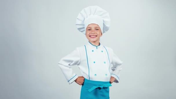 Portrét kuchaře vařit dítě 7-8 let, uvádí fajn kamera a usmívající se zuby stojí izolované na bílém