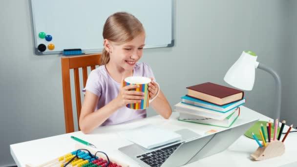 Portrét šťastný školačka 7-8 let drží šálek čaje a při pohledu na notebook a usmívá se zuby na kameru