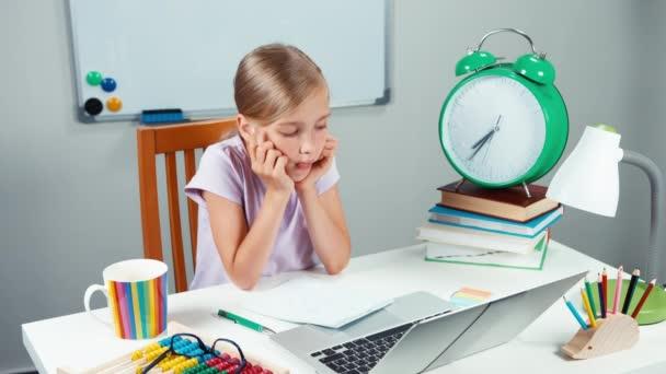 Portrét smutné student dívka 7-8 let, sedí v jejím stole a při pohledu na fotoaparát se bez úsměvu