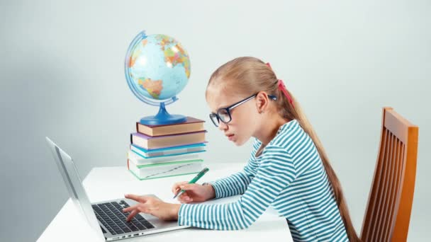 Portrét školačka pomocí její laptop a psaní v poznámkovém bloku. Dítě sedí u stolu a dělat domácí úkoly