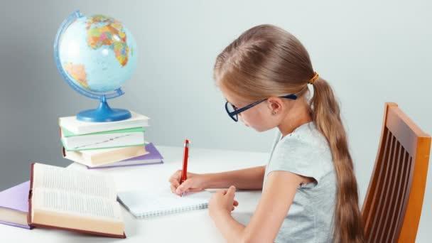 Iskola lány négy-szemét írásban a notebook és kamera mosolyogva. Gyermek ülő-on iskolapad elszigetelt fehér background