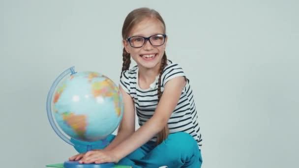 Školy dívka točí její zeměkoule a usmívá se na kameru izolované na bílém. Palec nahoru. Ok