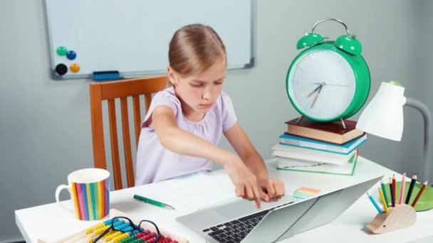 Škola dívka něco psát na notebooku velmi pomalu a usmívá se na kameru