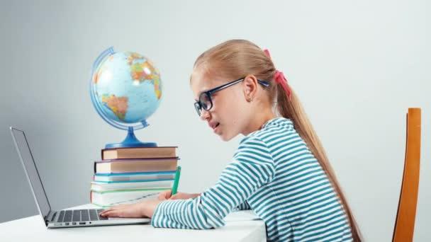 Iskola lány használ a laptop és notebook írásban. Gyermek ülő-on iskolapad elszigetelt fehér