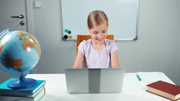 Školačka dítě 7-8 let pomocí její laptop v její stůl v učebně proti školní rada