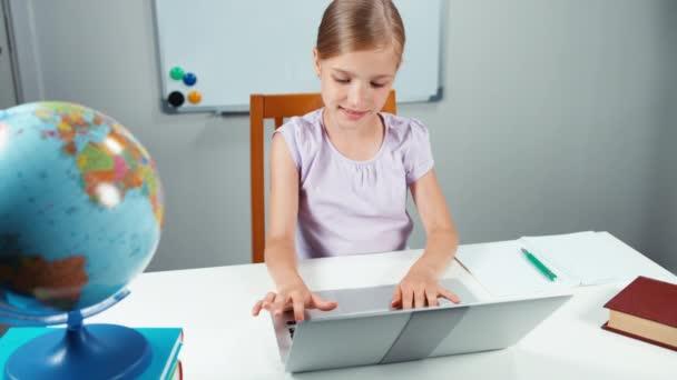 Iskolás gyerek 7-8 év használ vele laptop, az ő íróasztal osztályban olyan iskolaszék ellen. Szemközti nézet