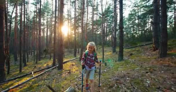 Hiker girl 8-9 years child goes at camera in the forest