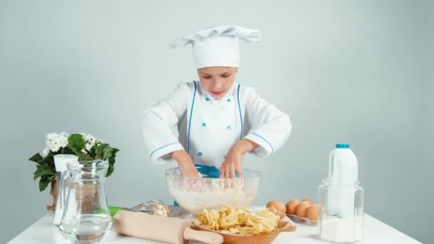 Mladí baker hrát s těsta a směje se na kameru izolované na bílém