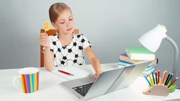 Schoolgirl holds her lollipop and typing something in her laptop sitting at the desk in the evening. Thumb up. Ok
