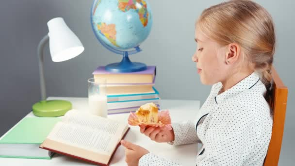 Portrait school girl 7-8 years reading book drinking milk and eating muffin sitting at the table
