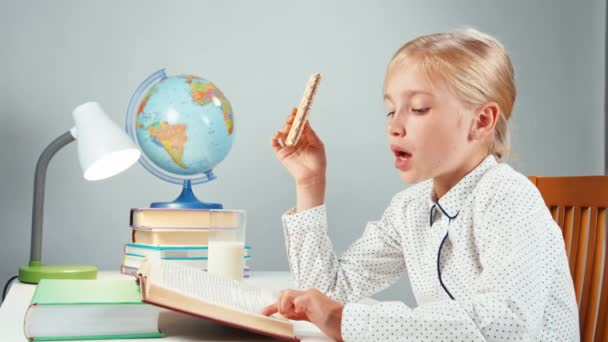 Portrét profil blond školačku 7-8 let, čtení knihy jíst oplatka sedí u stolu, izolované na bílém v noci