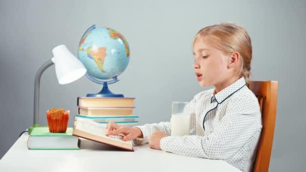 Schulmädchen 7-8 Jahre lesen Buch, trinken Milch und lächeln in die Kamera isoliert auf weiß. Daumen hoch. ok