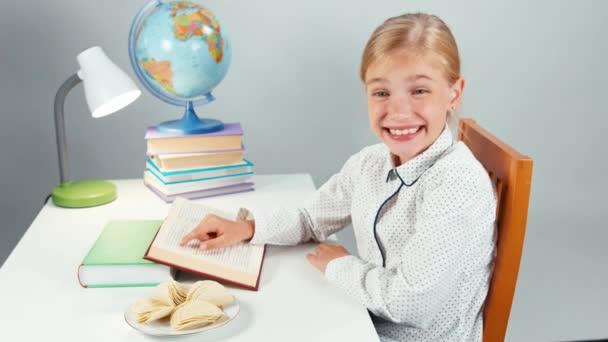 Školačka brambůrek a čtení učebnice u stolu večer