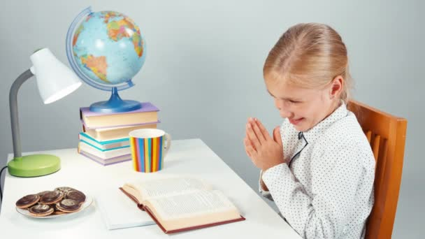 Školačka dítě čte knihu večer a jíst čokoládové cookies. Palec nahoru. Ok