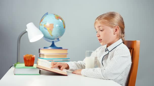 School girl 7-8 years reading book sitting at the table on white background