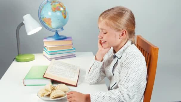 Školačka brambůrek a čtení učebnice u stolu večer izolované na bílém