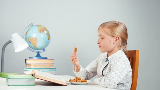 Portré profil szőke iskolás lány étkezési cukorka ül az asztalnál, az éjszaka elszigetelt fehér könyv olvasó 7-8 év