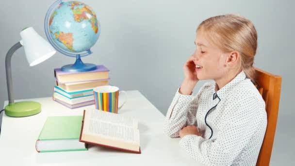 Portrét žák dívka pití čaje a strečink. Dítě sedí u stolu, izolované na bílém