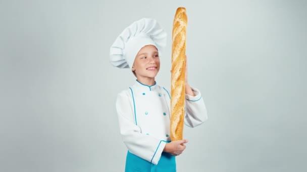 Baker lány 7-8 éves gyermek tart kenyér baguette, és mosolyogva kamera