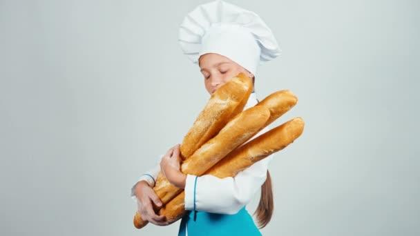 Mladí baker dívek drží chléb bagety a usmívá se na kameru izolované na bílém