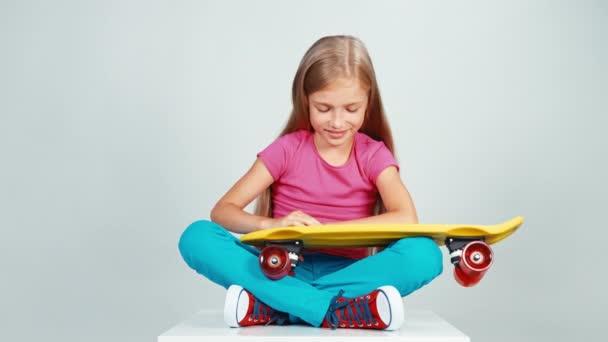 Porträt Schulmädchen schaut auf Groschen-Skateboard und sitzt auf dem Boden