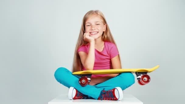 Portrét školačka při pohledu na penny skateboard a sedí na podlaze. Palec nahoru. Ok