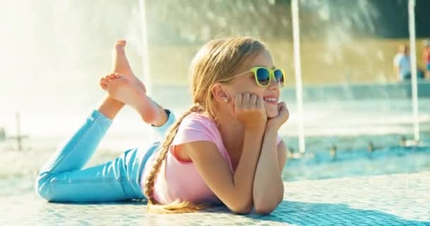 Child lying on fountain background at sunny day and waving hand