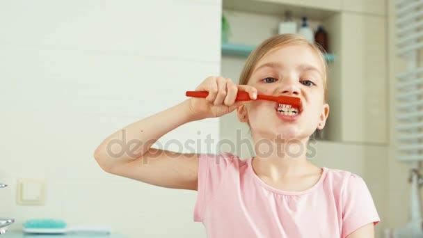 Zblízka portrétní dítě dívka 7-8 let čištění zubů v koupelně a při pohledu na fotoaparát. Zvětšení/zmenšení