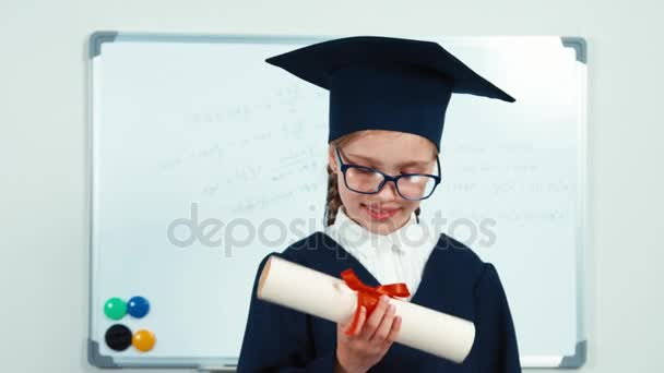 Cute student 7-8 years graduate in the mantle and hat. Child looking at camera through diploma and smiling with teeth near whiteboard. Slider. Zooming