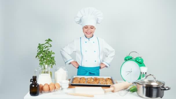 Happy kuchaři vařit dívek 7-8 let má pekáč s sušenky a usmívá se na kameru. Izolované na bílém. Zvětšení/zmenšení