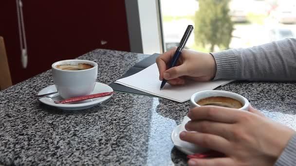 Kávét iszik, és írásban valami kávézóban üzleti terv