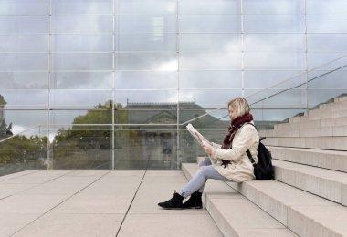 beautiful young woman reading newspaper