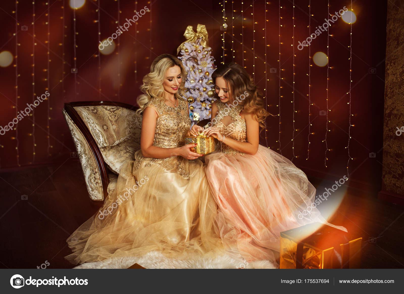 Schöne junge Mutter und Tochter tragen Mode goldene Kleider in der ...